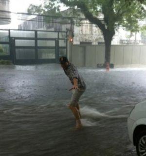 Ashton Kutcher surfa pelas ruas de São Paulo após chuva