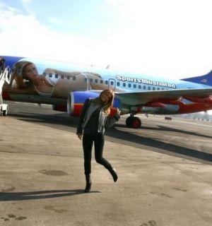 Modelo Bar Refaeli posa em frente a avião pintado com sua foto